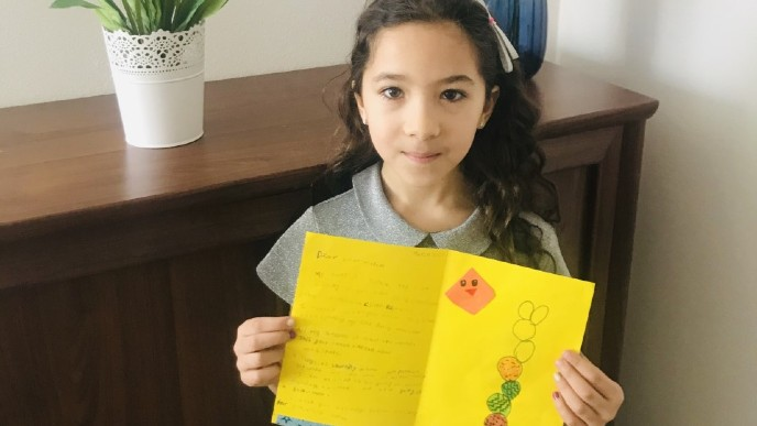 PORG International School pupil with a greeting card made for an isolated senior in Britain.